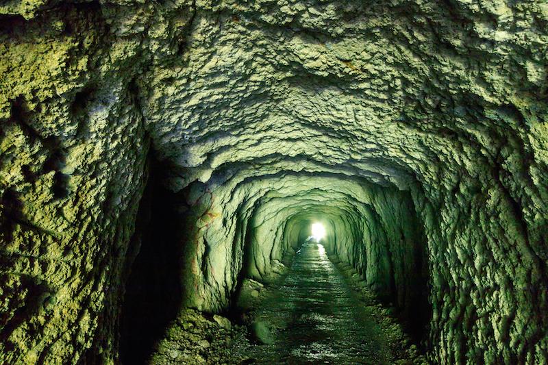 大鮫に通じるトンネルは幅、高さとも約2.5㍍、全長60㍍ほど。出口に向かって歩くうちに71年の時間を遡っているような錯覚に襲われた(佐瀬雅行撮影)