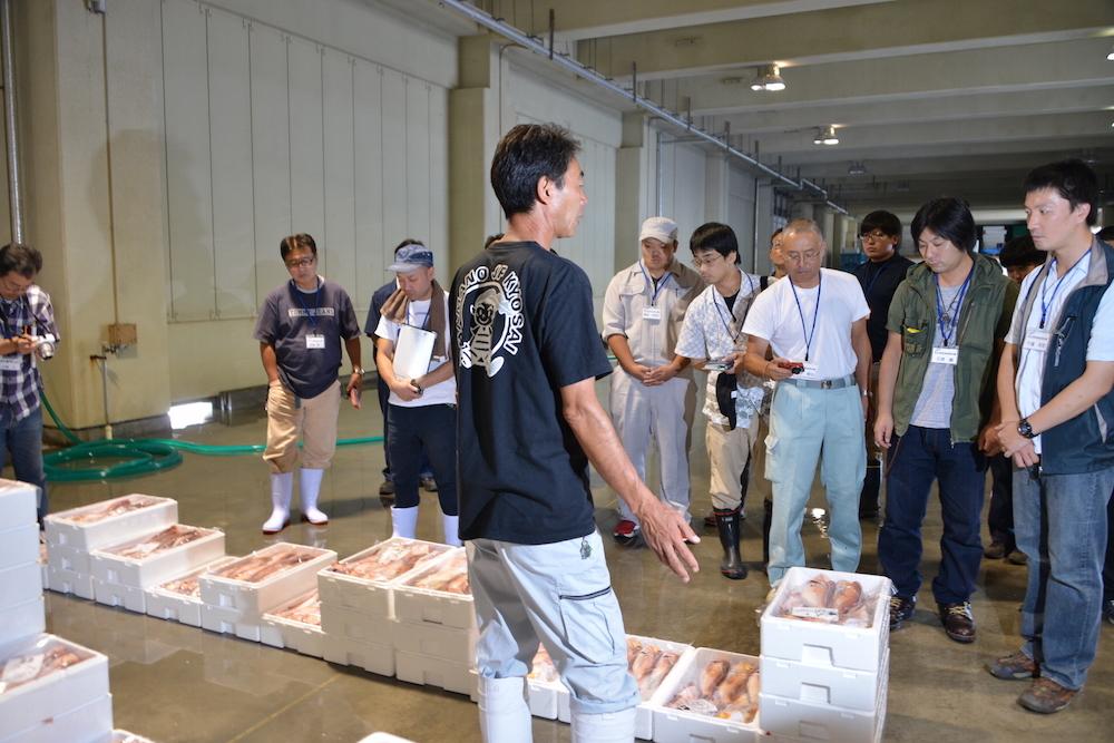 競りが始まる前に漁協職員から説明を聞く(鐙啓記撮影)