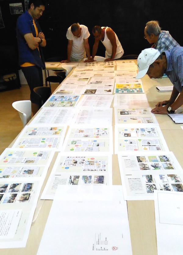 原稿を確認する編集委員の皆さん。制作期間は、3月から9月までの約半年にわたった=2016年9月、南蒲生町内会集会所(葛西淳子撮影)