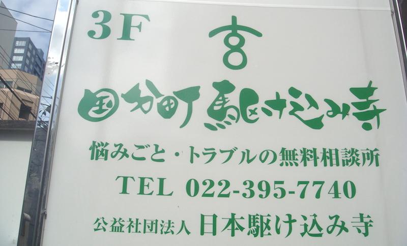国分町のビルにある「日本駆け込み寺 仙台支部」の看板(阿部えりこ撮影)