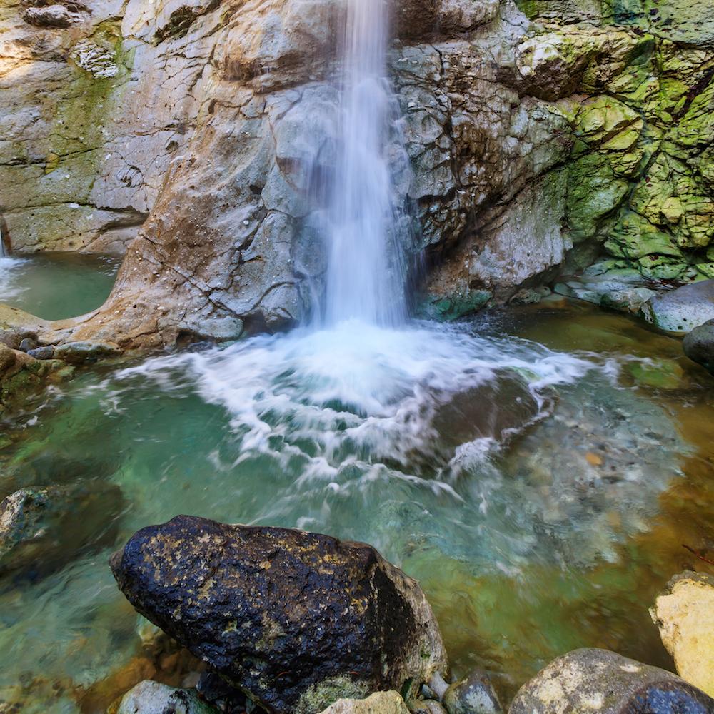 源泉は98度の高温で強酸性だが、沢水と混じって滝つぼでは適温になる。入浴適期は7月上旬〜9月中旬。水着着用で無料で入浴できる。近くに脱衣所が設けられている(佐瀬雅行撮影)