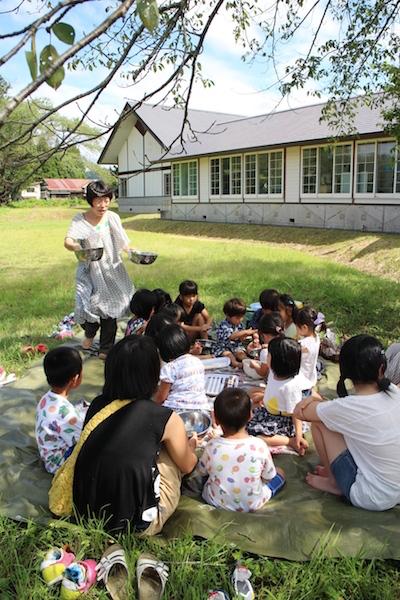 講演会中、子供たちは野外でお菓子つくり