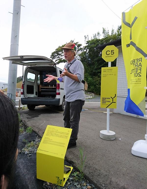 伏見家納屋の前で説明をするワタリウム美術館の和多利氏。奥の車の中に映像作品が展示されている。