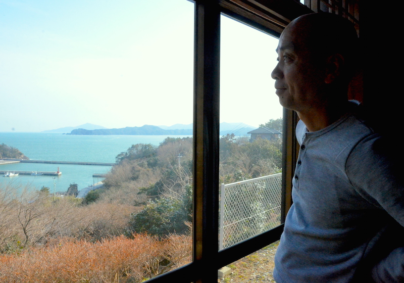 「民宿いずしま」の広間の大きな窓から外を眺める、佐藤淳さん