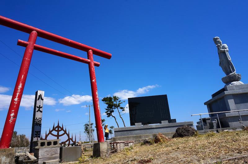 津波に耐え抜いた鳥居と、震災後に慰霊碑として建てられた観音像。新旧のこの地を守る神仏だが、鳥居は海を向き、観音像は海に背を向けている。