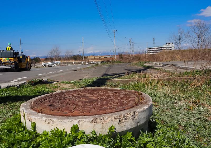 土(地面・コンクリート)がえぐられた状態のマンホール(下水管?)植物が成長しているため、初めは露出の違和感に気付きませんでした。でもこんなにえぐられるなんて…家(建築物)だけじゃなく地面もなんて…津波の力のすごさを感じました(右方向に、震災遺構・旧荒浜小学校)