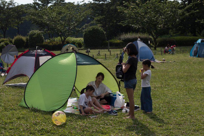 カラフルなテントが所狭しと並ぶ都内の公園(小林知史撮影)