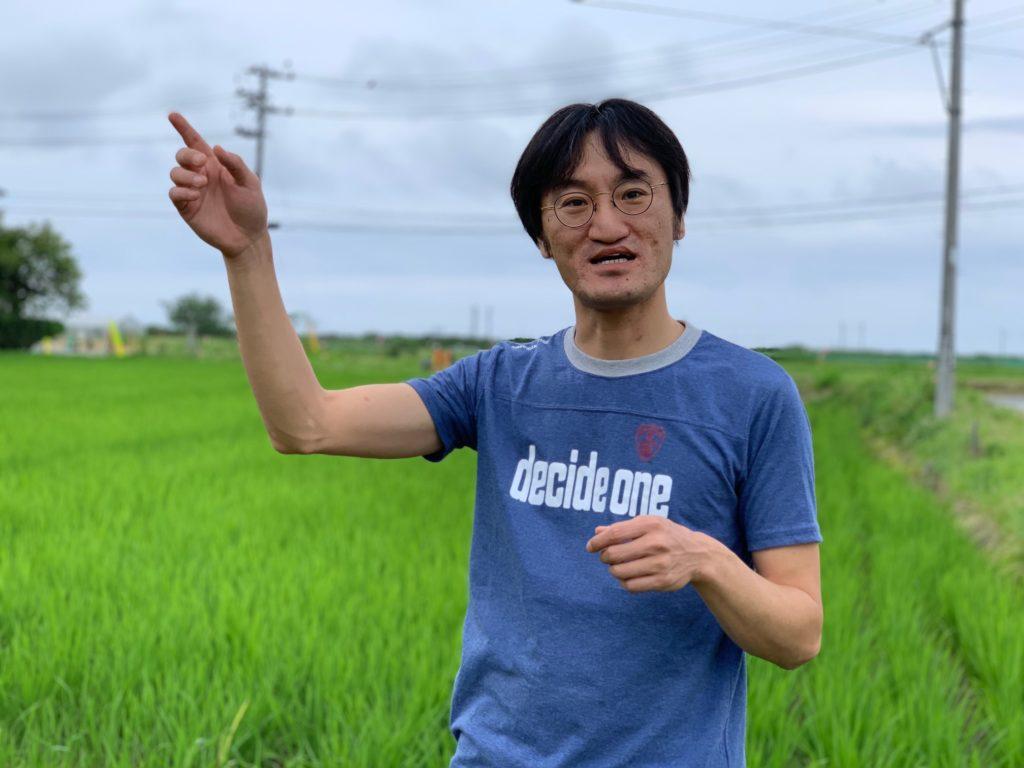 「ここに暮らす一人として地域の未来を考えていきたい」と話す吉川彰浩さん。自作のコメを育てている福島県楢葉町の田んぼの前で。