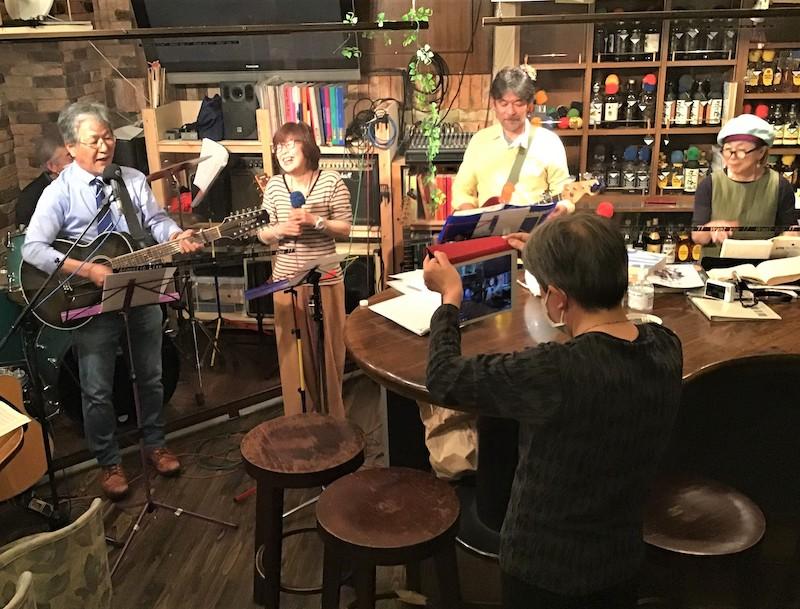 バンド仲間と店からライブ配信をする上野さん(左端)=5月3日